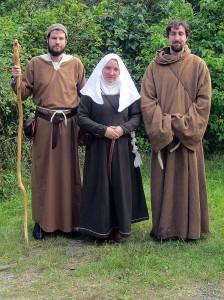 Moder Elarka, abbedissa vid Örnevalls kloster och en av ledarna för Nyckelns väktare, flankerad av två anselmitbröder från klostret.   Till vänster broder Asulf, också en av Nyckelns väktare; till höger broder Arnulf, numera biktfader hos grevinna Eleonora Drakvinge.  Foto: Theo Axner, 2015