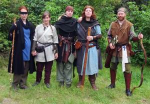 Fem av de sex från båda sidor som överlevt resan på andra sidan porten. Resan hade slutit dem hårt samman trots att de börjat den som fiender.   Från vänster: Fenri, f d Rödkåpa; Ingrid Sivsdotter, margholisk motståndskämpe; Rakel, f d Salamander; adept Kari, gedansk magiker; Eskil Bursson, gedansk spejare för Nyckelns Väktare.  Foto: Theo Axner, 2015
